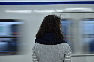 Image of woman standing on platform and subway train passing